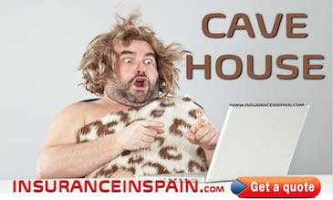 Cave man looking at computer with a surprised look on his face as he finds Cave house insurance in Spain