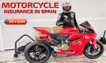 Motorcycle racer standing besides a red Ducati Panigali in the pits at a racetrack in Valencia